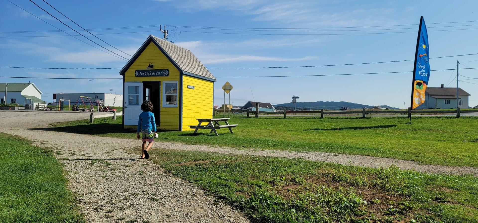 child walking to yellow house on Site de la Cote