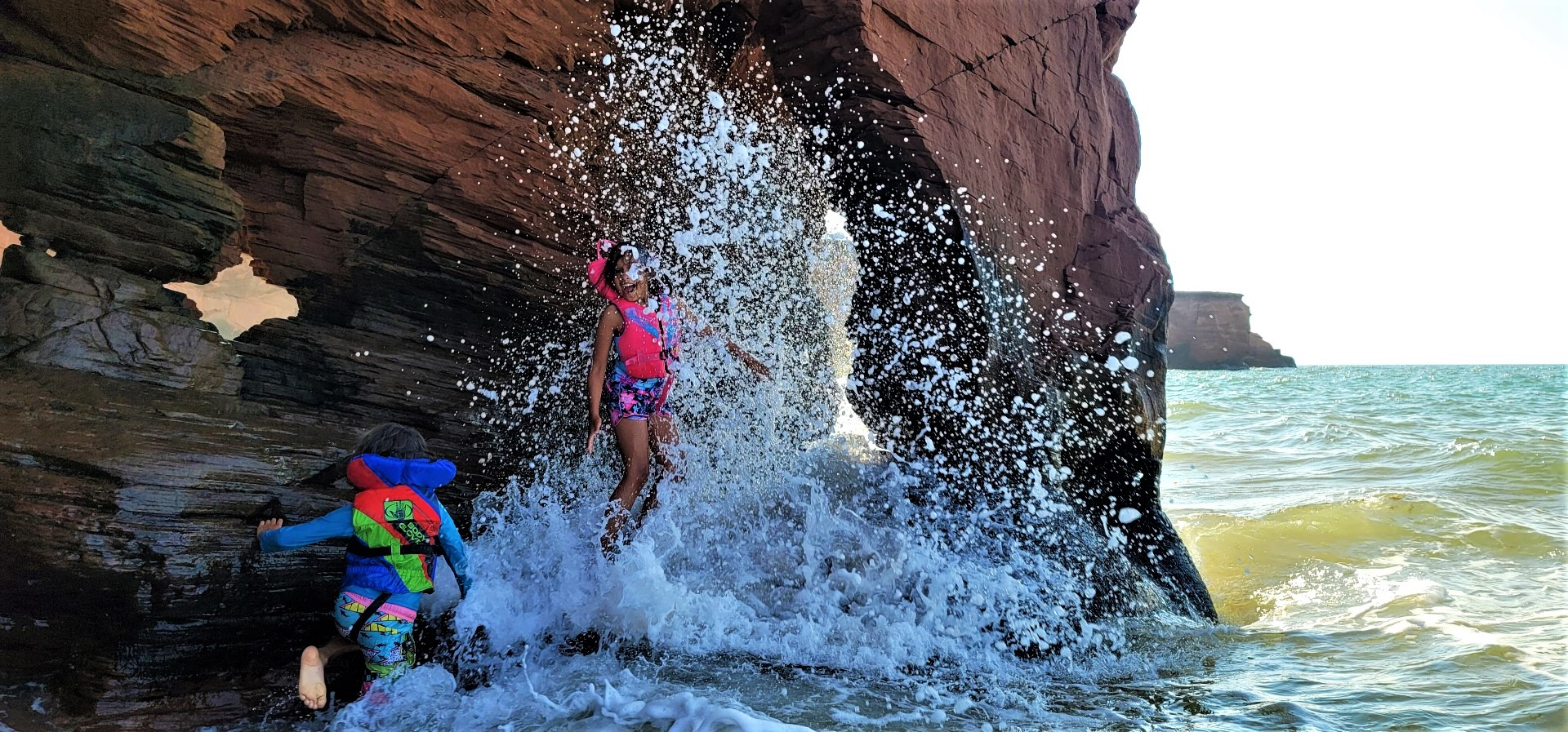 kids splashed by a wave in a red cave