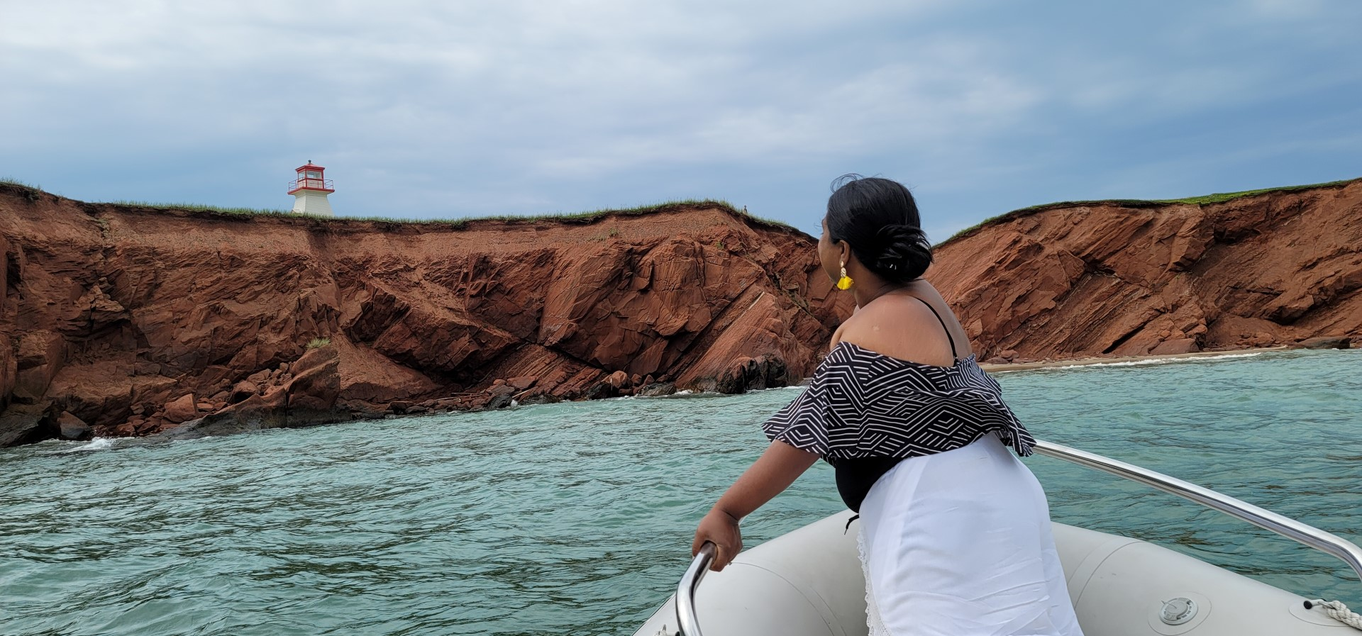 Lady looking on a boat looking at red cliffs and blue water