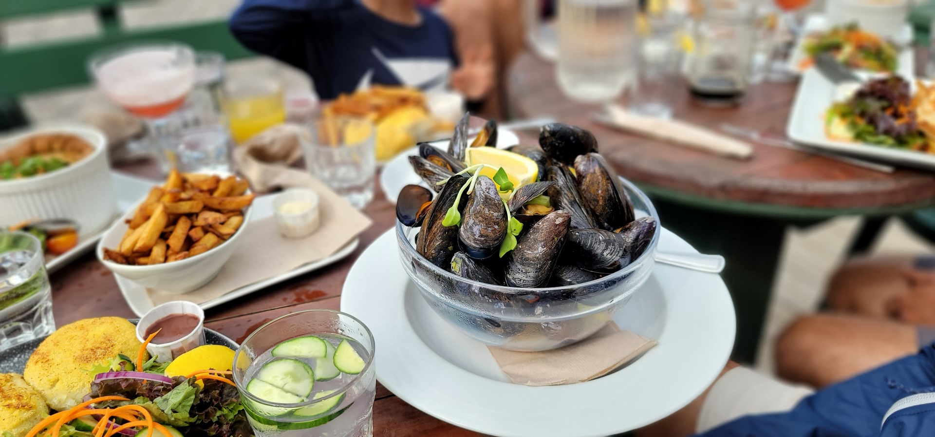 mussels in a bowl on a table with food