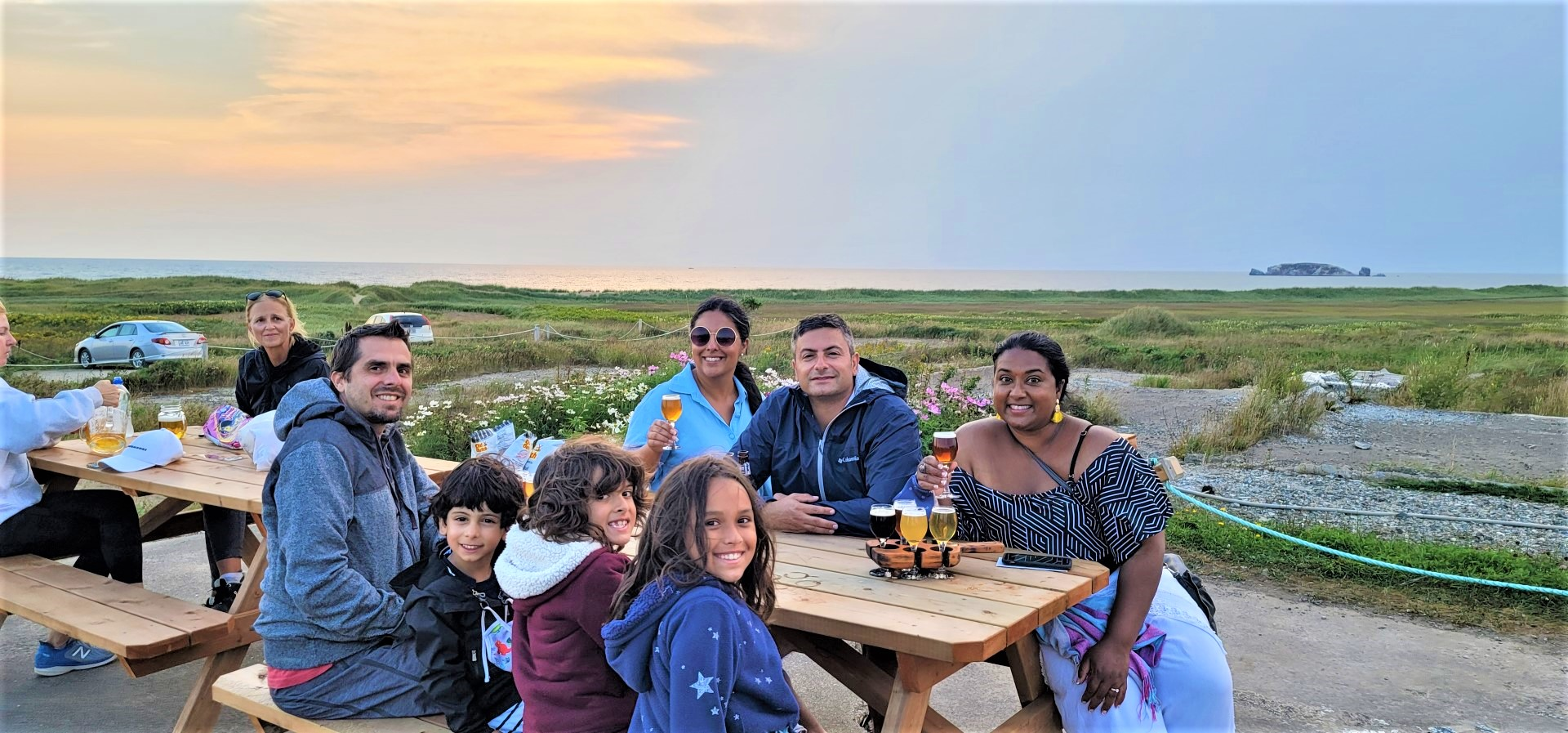 group smiling at camera during sunset at Magdalen Islands brewery