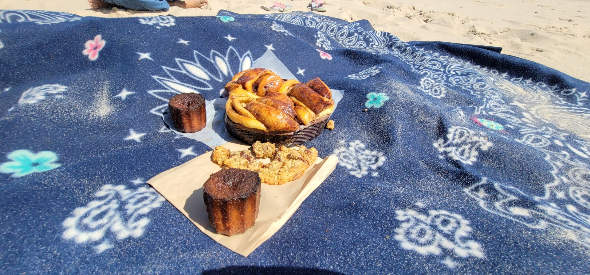 canelles and pastries on a blue sandy blanket