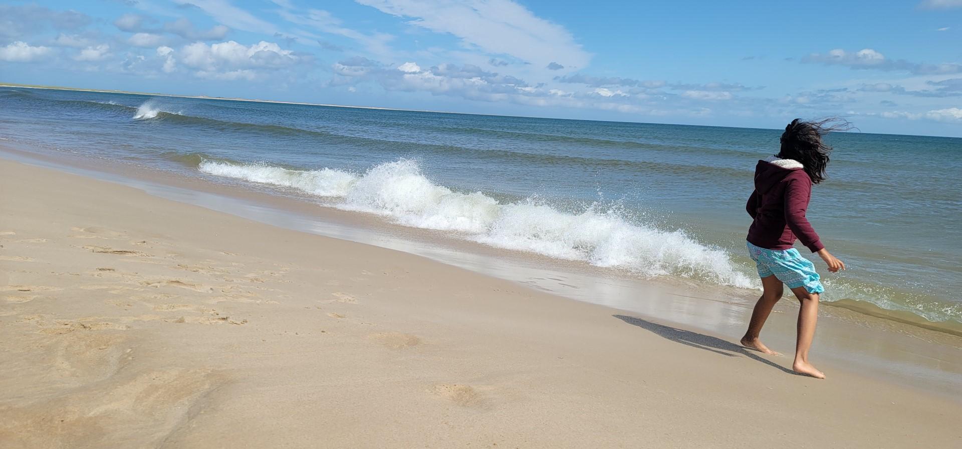 child running from waves at Grande Échouerie Beach