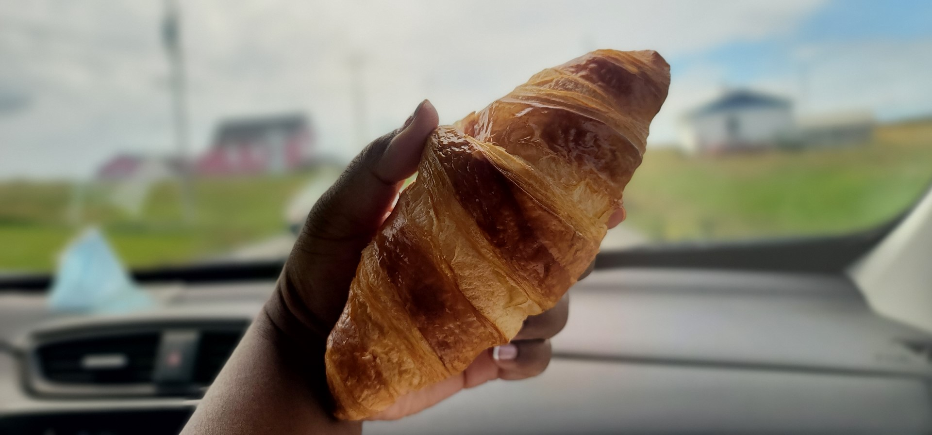 brown hand holding a croissant in front of window