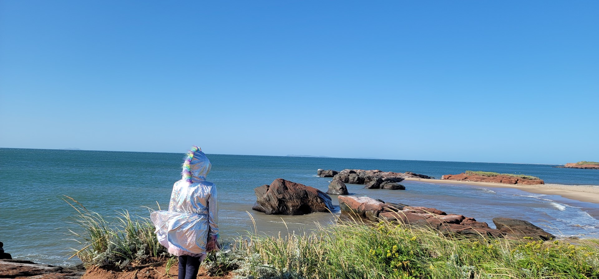 Child in silver jacket looking at water from Boudreau Island