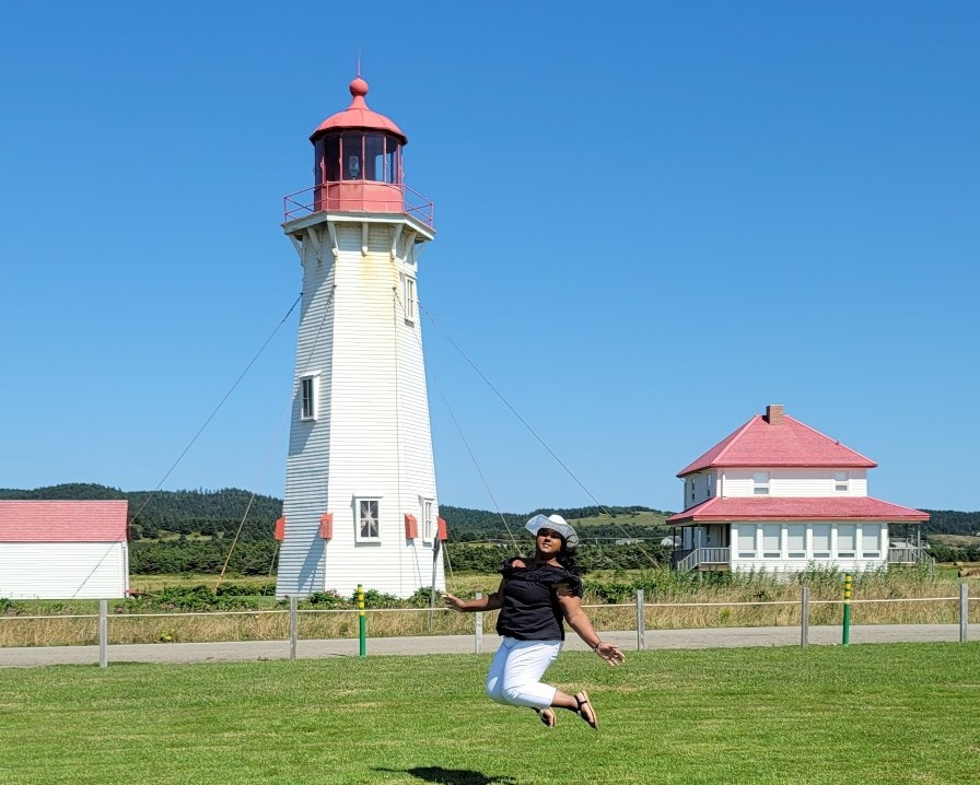 lady in white pants and black top jumping in front of Anse la cabane lighthouse