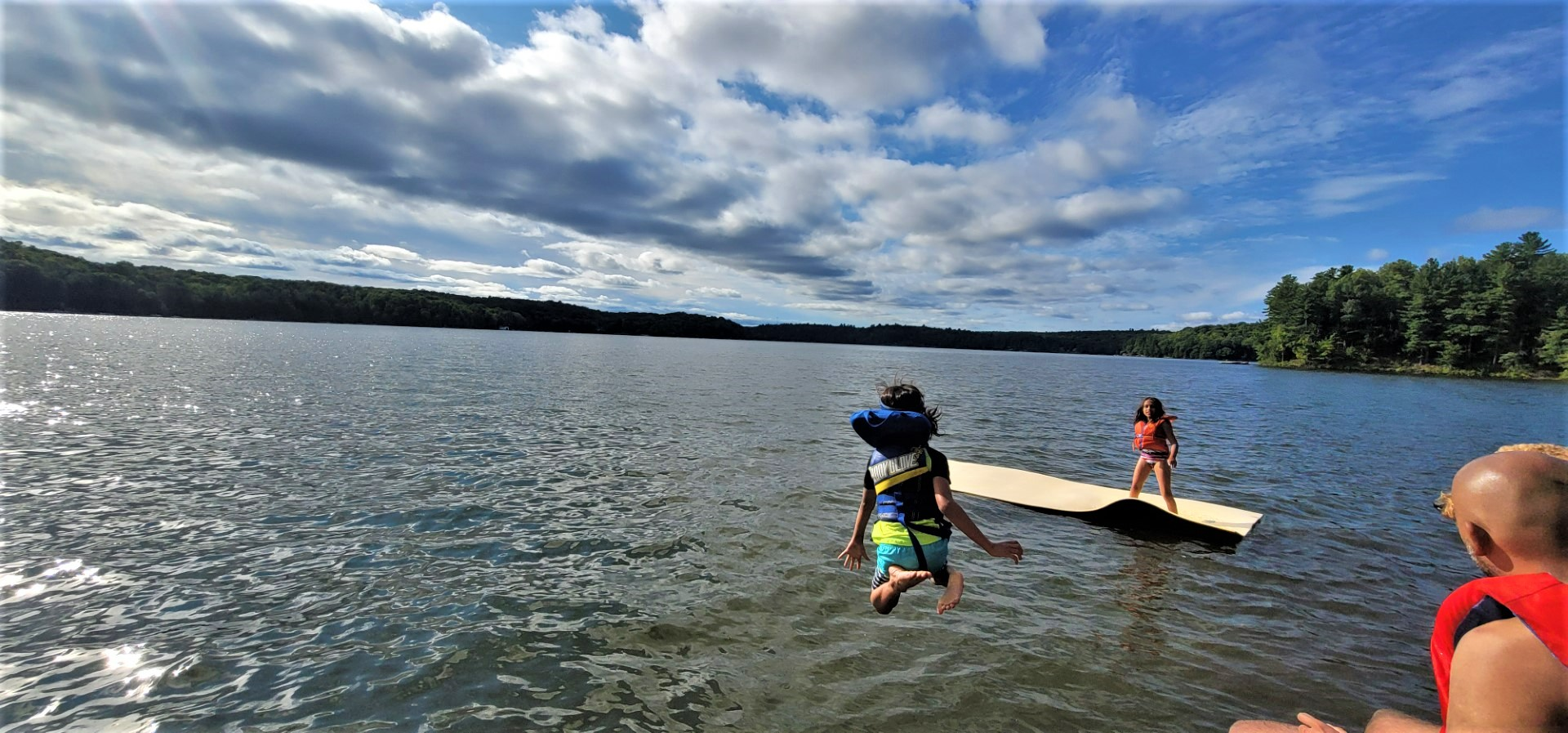 children jumping into lake on a clear day with white clouds and blue skies