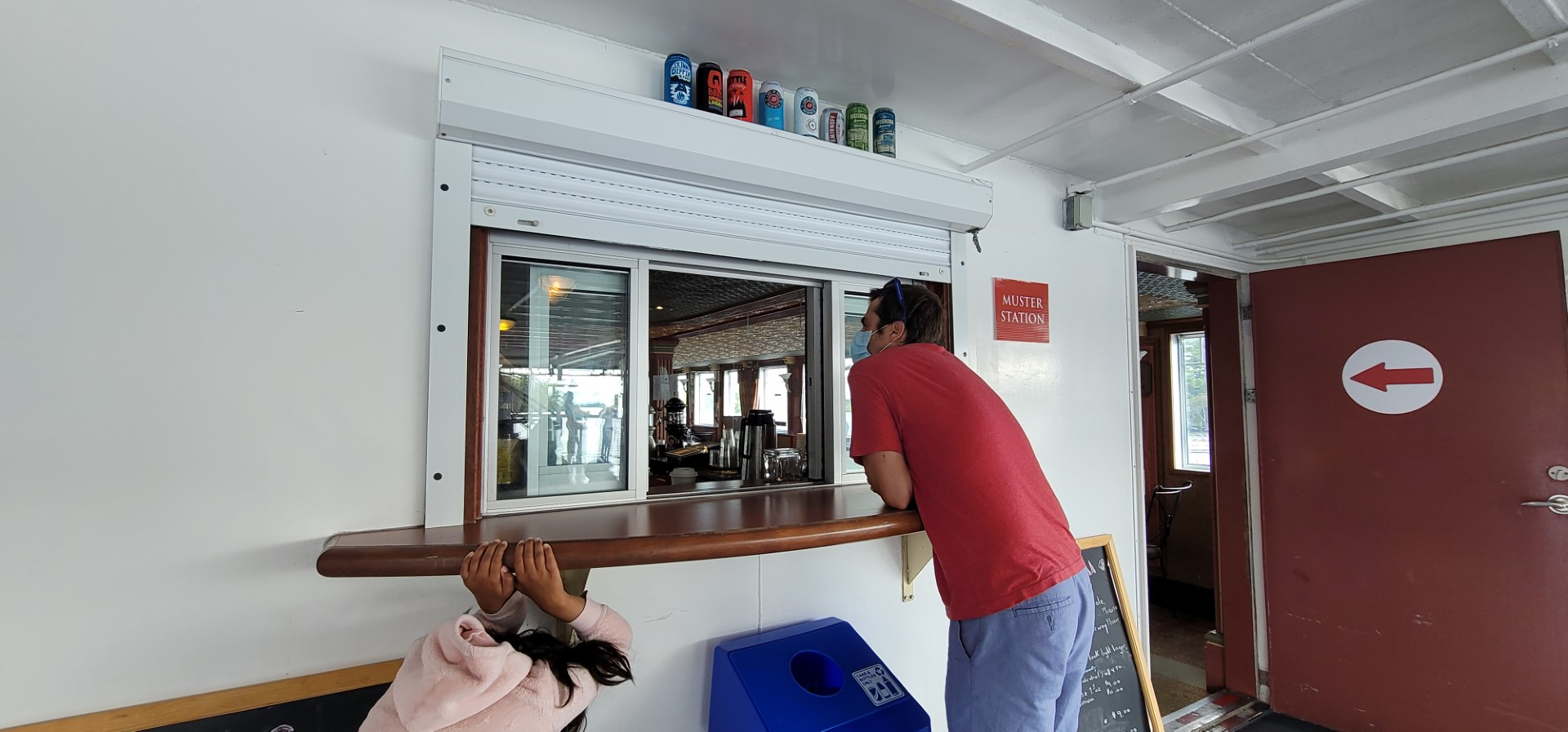 person in red shirt and blue shorts waiting at ship deck window for drinks