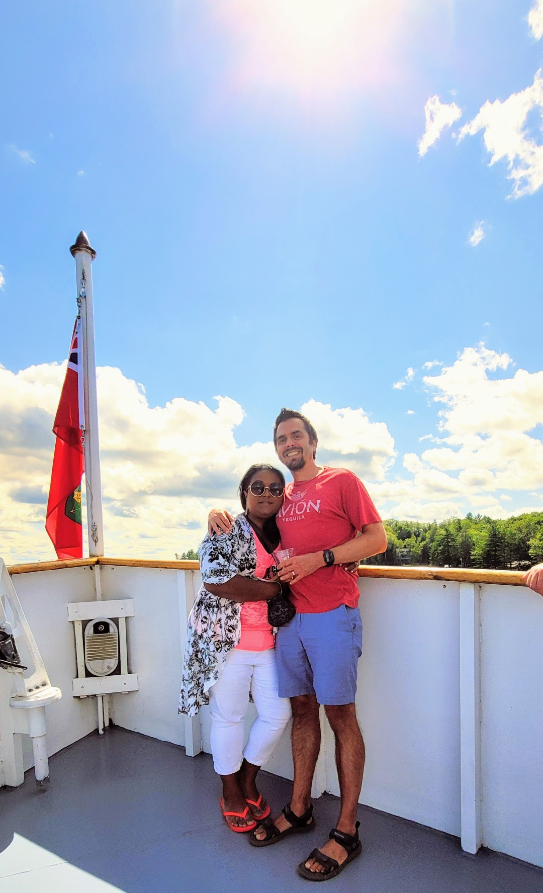 mixed race couple on a boat with Canadian flag in Muskoka
