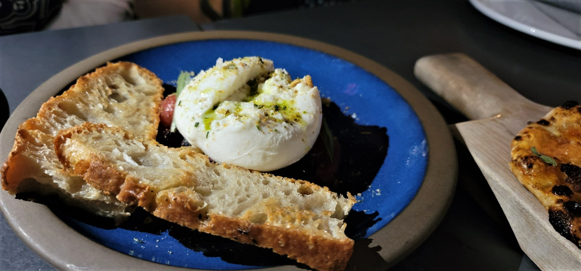 white burratini with bread on blue plate