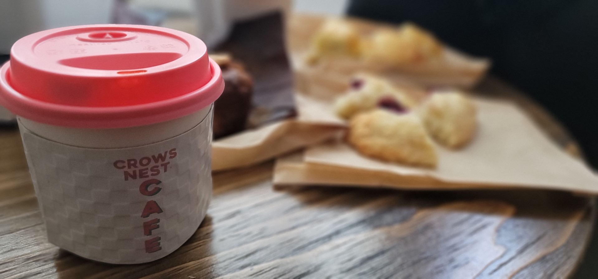 pink lid on coffee cup with words Crows Nest
